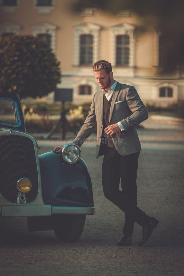 Uomo ricco sicuro vicino al convertibile classico fotografia stock libera da diritti