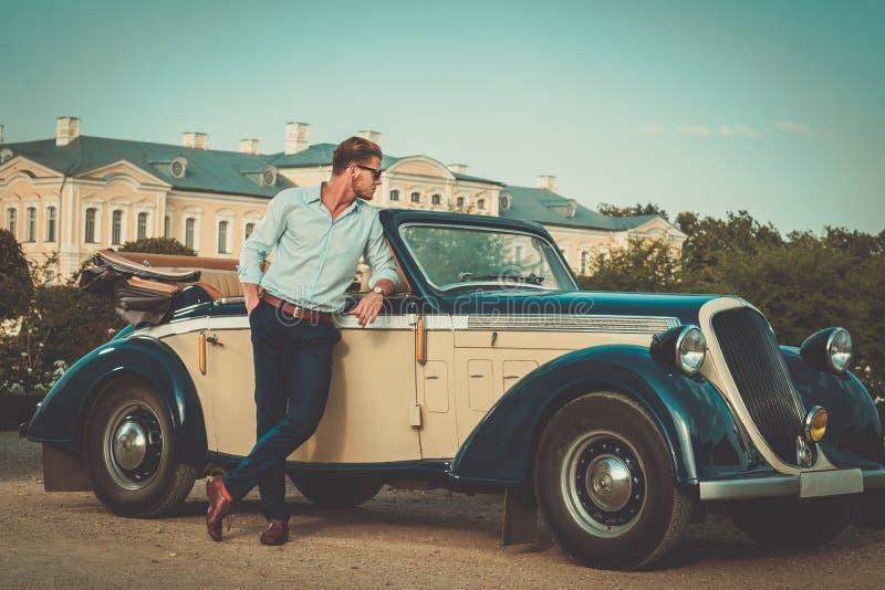 Uomo ricco sicuro vicino al convertibile classico fotografie stock