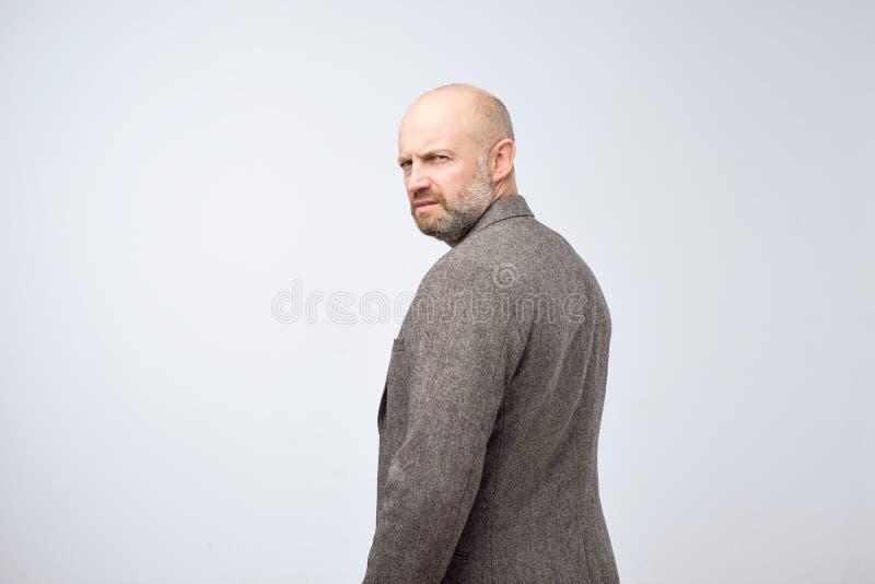 Uomo rigoroso severo con la barba in vestito casuale che gira indietro fotografie stock libere da diritti