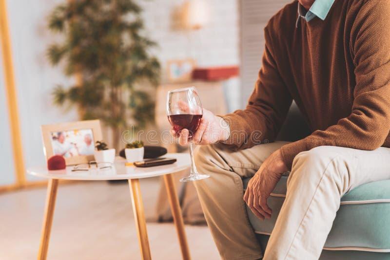 Uomo rispettoso che beve vino rosso che gode della sera piacevole immagine stock libera da diritti