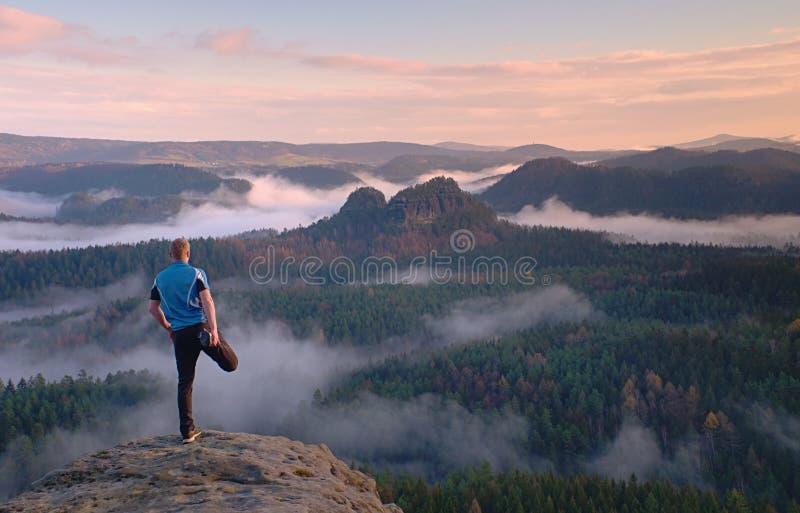 Uomo in rivestimento caldo con lo zaino nelle montagne del rockx di primavera fotografia stock libera da diritti