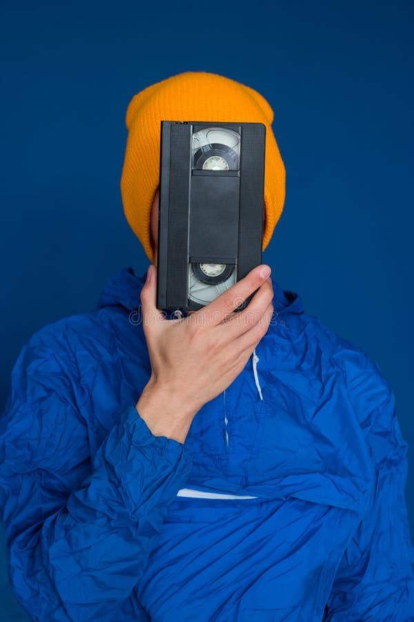 Uomo in rivestimento di sport 90s e cappello giallo con la cassetta di VHS su fondo blu fotografia stock libera da diritti