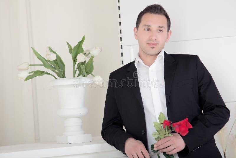 Uomo romantico con una rosa rossa fotografia stock