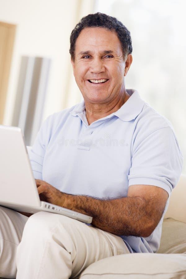 Uomo in salone con sorridere del computer portatile immagine stock libera da diritti