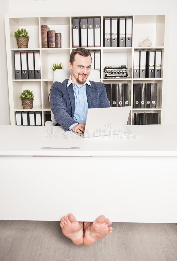 Uomo scalzo felice di affari che lavora nell'ufficio immagini stock libere da diritti