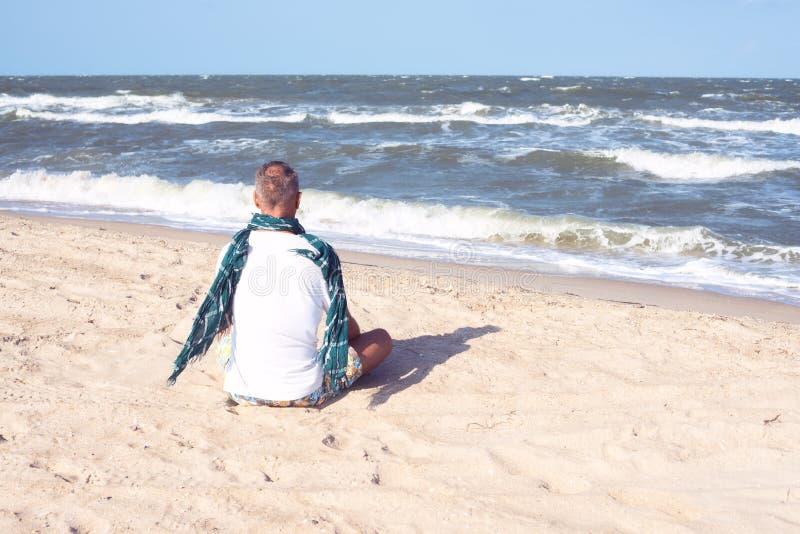 Uomo in sciarpa che si siede sulla spiaggia fotografia stock libera da diritti
