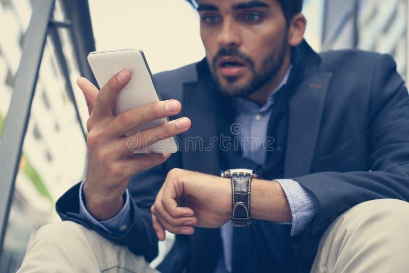 Uomo scioccante di affari che per mezzo del cellulare e dell'orologio Fine in su fotografia stock libera da diritti