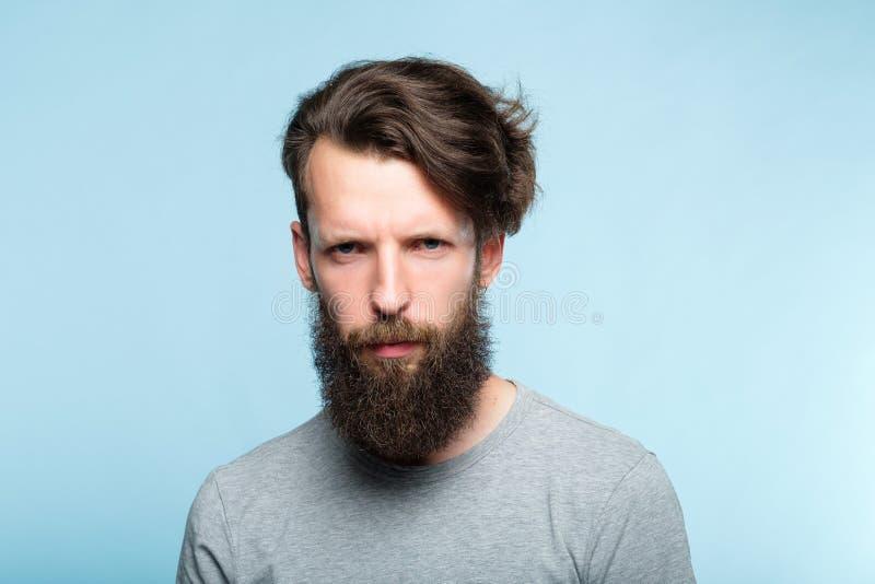 Uomo scontroso aggrottante le sopracciglia serio di espressione di emozione fotografia stock