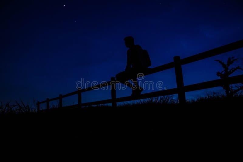 Uomo scuro che sogna su un recinto alla notte fotografia stock libera da diritti