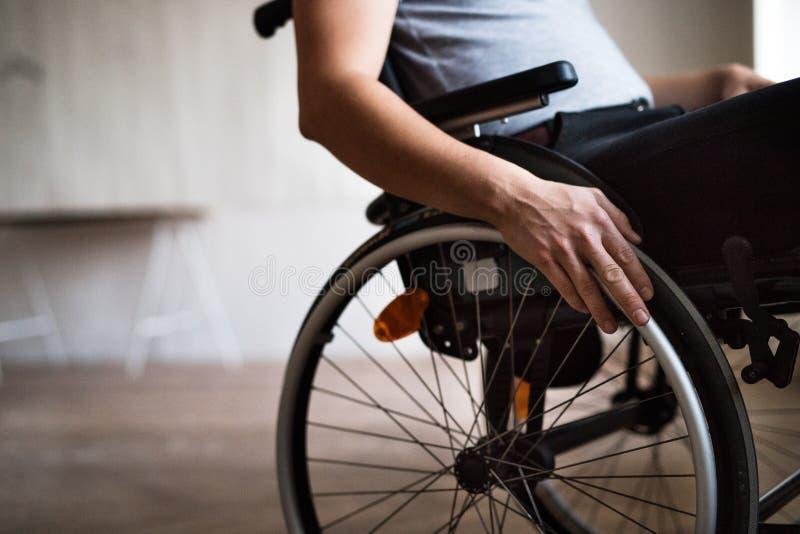 Uomo in sedia a rotelle a casa o in ufficio fotografia stock libera da diritti