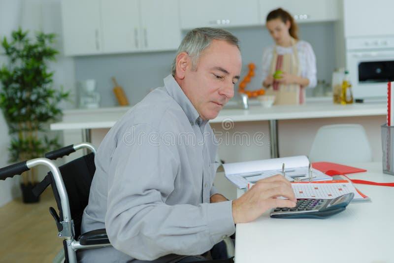 Uomo in sedia a rotelle che fa il lavoro d'ufficio a casa immagini stock libere da diritti