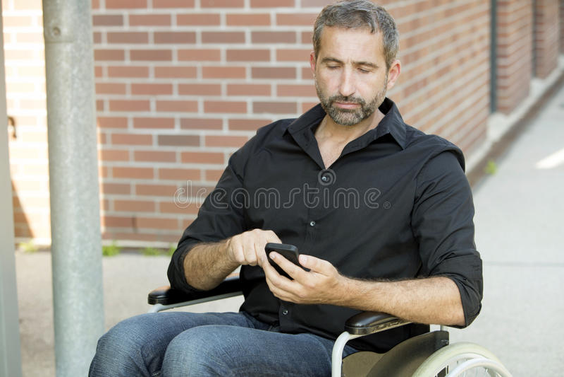 Uomo in sedia a rotelle che manda un sms sul suo telefono immagine stock libera da diritti