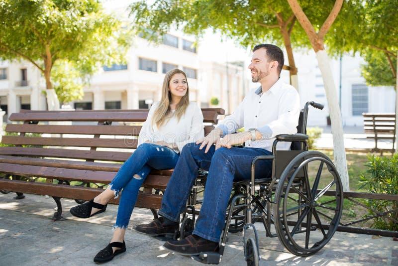 Uomo in sedia a rotelle con la sua amica immagini stock libere da diritti