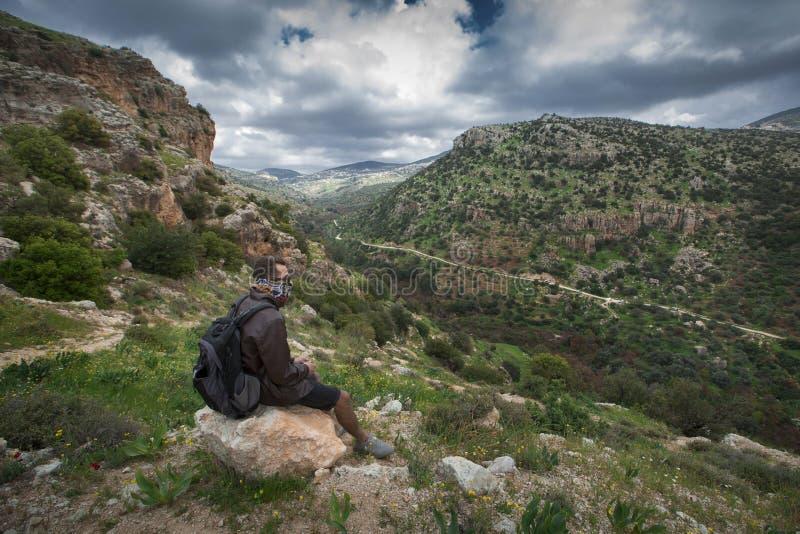 Uomo seduto sulla collina di Brown Boulder Top fotografie stock libere da diritti