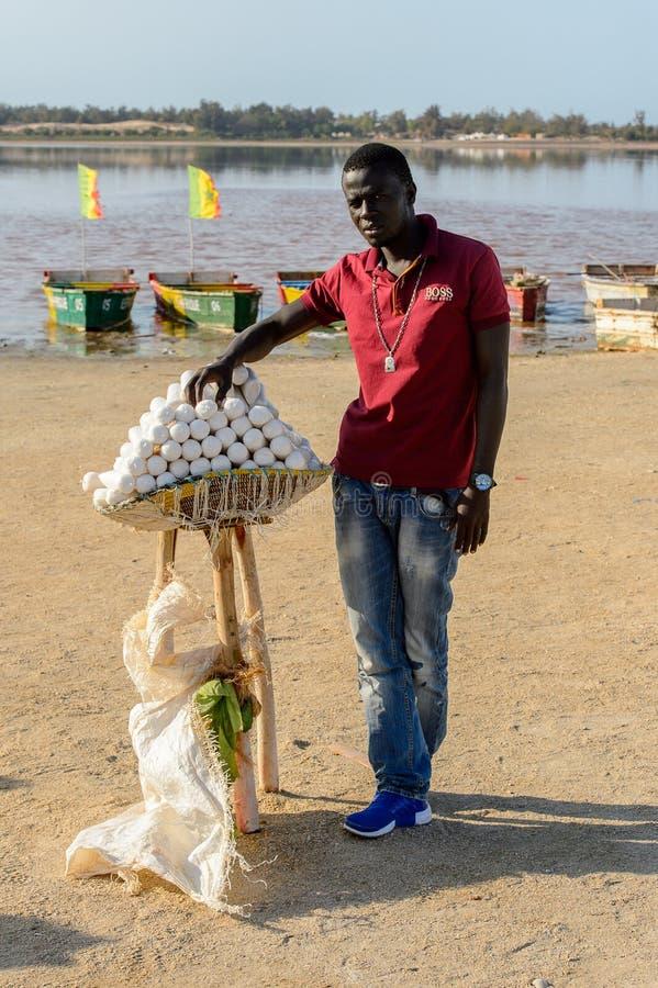 Uomo senegalese non identificato nei supporti rossi dei jeans e della camicia su Th fotografia stock libera da diritti