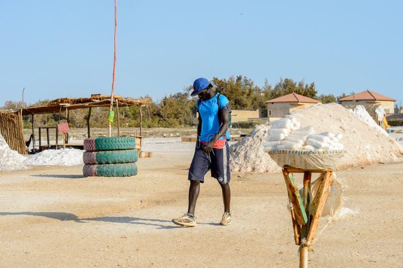Uomo senegalese non identificato nelle passeggiate blu del cappuccio e della camicia sul fotografie stock libere da diritti
