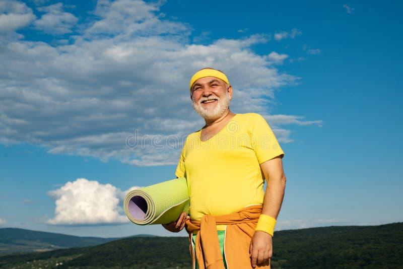 Uomo senior adatto che riposa dopo avere risolto Allenamento attivo di sport per la persona anziana Lo sportivo anziano sportivo  fotografia stock