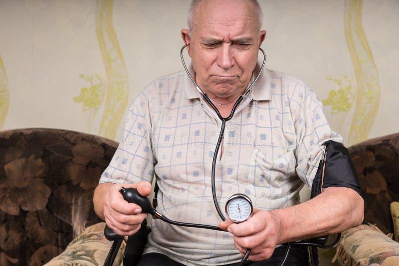 Uomo senior aggrottante le sopracciglia che controlla la sua pressione sanguigna immagine stock