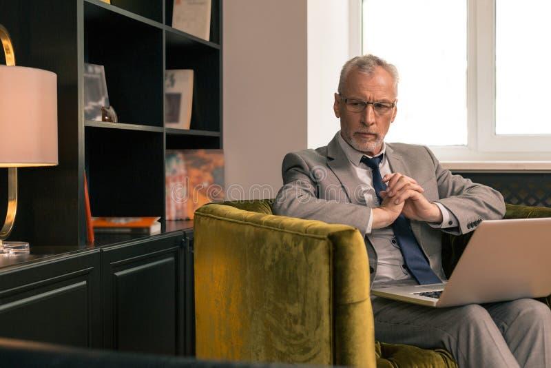 Uomo senior alla moda caucasico premuroso che si siede nel suo ufficio fotografie stock libere da diritti