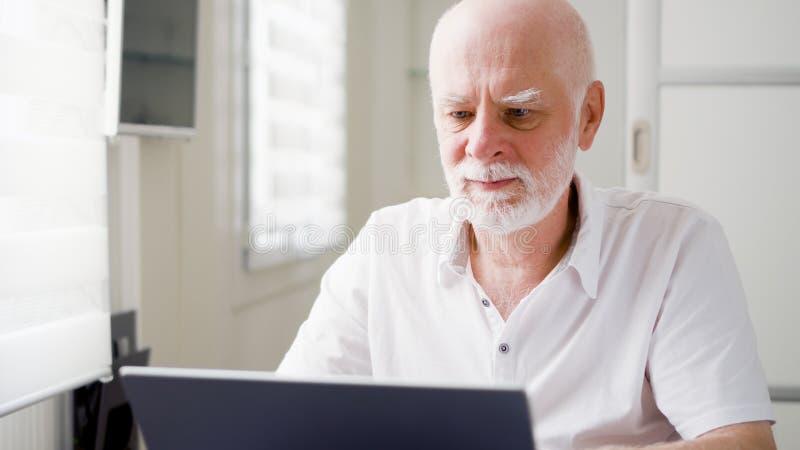 Uomo senior anziano bello che lavora al computer portatile a casa A distanza freelance il lavoro sul pensionamento immagini stock