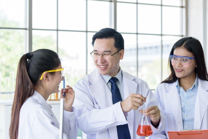 Uomo senior asiatico dello scienziato del laboratorio che lavora al laboratorio con il giovane backgroud asiatico dello scienziat immagine stock