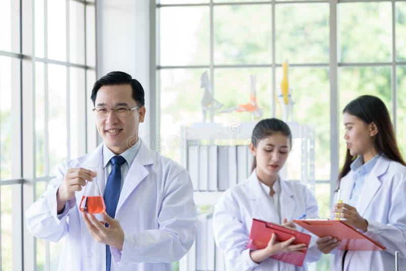 Uomo senior asiatico dello scienziato del laboratorio che lavora al laboratorio con il giovane backgroud asiatico dello scienziat fotografia stock libera da diritti
