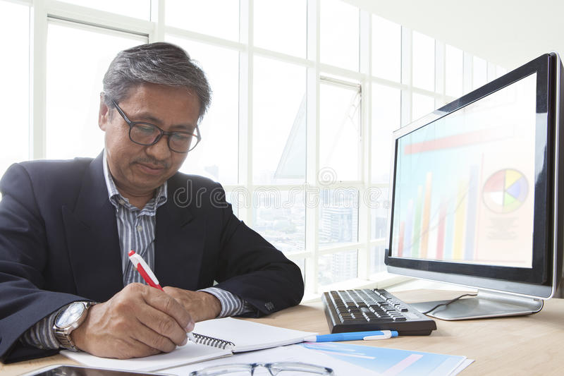 Uomo senior asiatico di affari che lavora alla tavola del computer per l'ufficio l fotografie stock libere da diritti