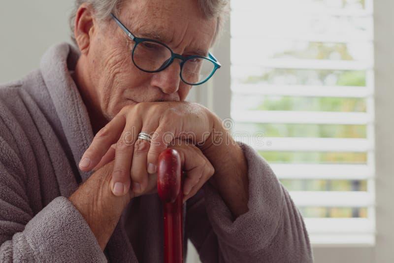 Uomo senior attivo che si appoggia canna di camminata in una casa comoda fotografia stock