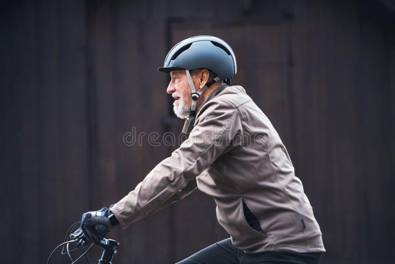 Uomo senior attivo con il fondo scuro di riciclaggio dei againts di aria aperta del casco della bici fotografia stock