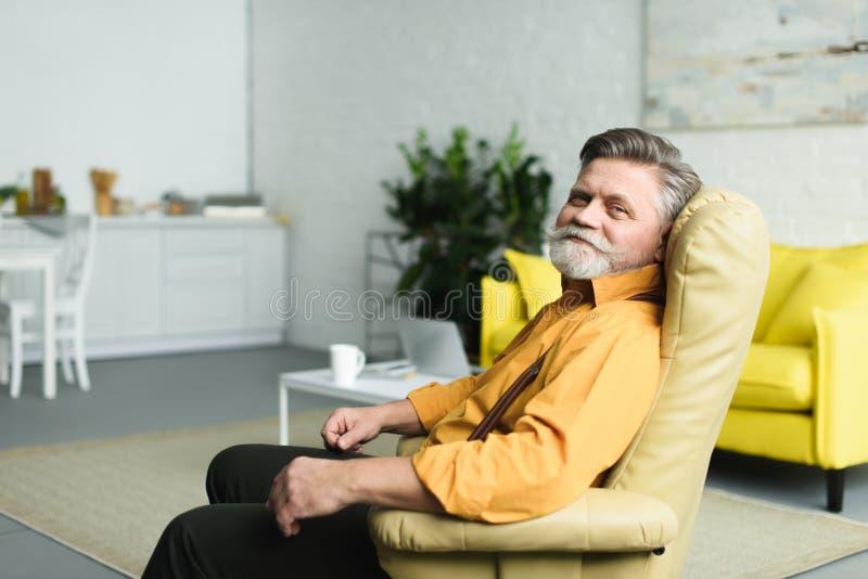 uomo senior barbuto bello che sorride alla macchina fotografica mentre sedendosi in poltrona fotografie stock libere da diritti