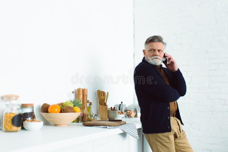 uomo senior barbuto che parla dallo smartphone mentre stando alla cucina immagini stock libere da diritti
