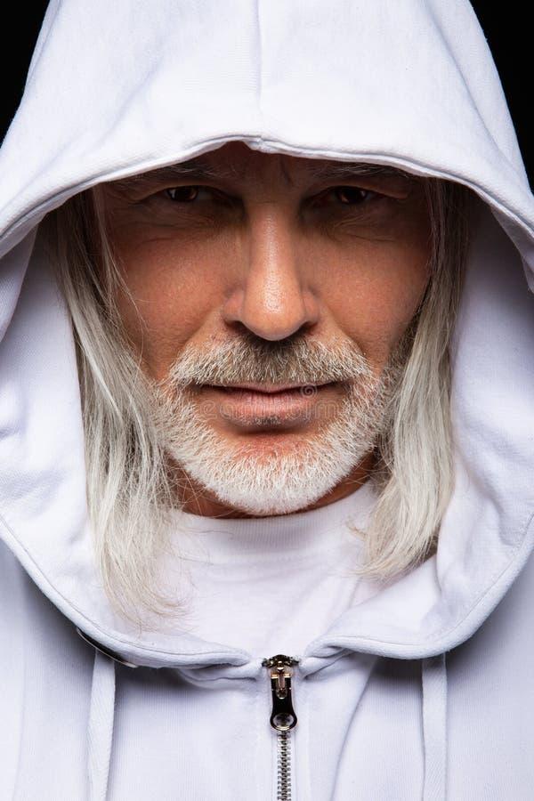 Uomo senior barbuto sotto il cappuccio fotografie stock libere da diritti