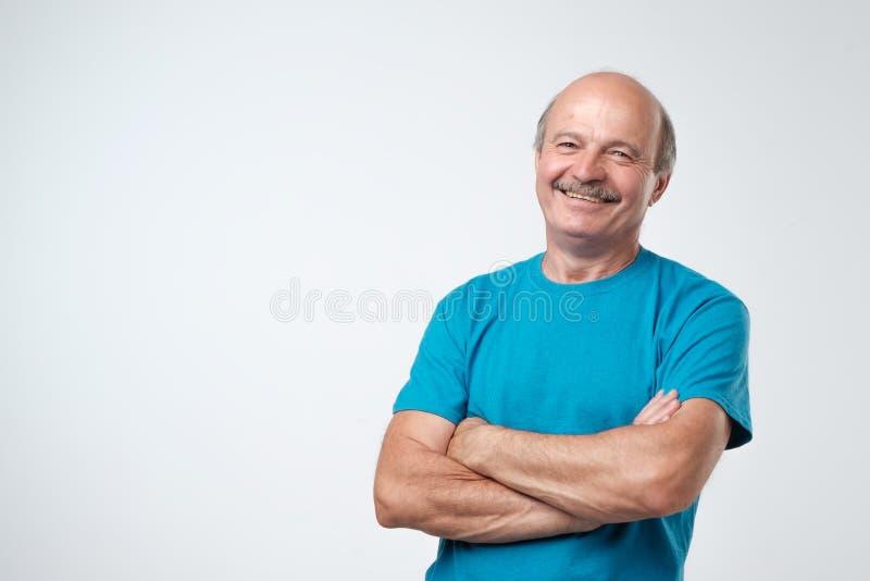 Uomo senior bello affascinante in abbigliamento casual che tiene armi attraversate e sorridere fotografie stock libere da diritti