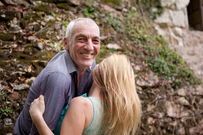 Uomo senior bello che abbraccia la sua giovane amica all'aperto e che sorride esaminando la macchina fotografica fotografie stock libere da diritti
