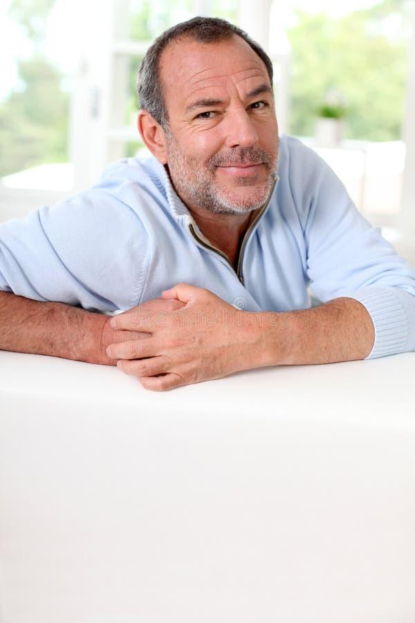 Uomo senior bello che sorride appoggiandosi sofà fotografie stock libere da diritti