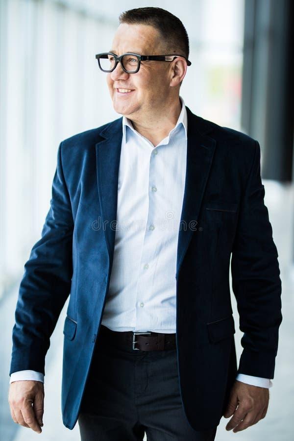 Uomo senior bello e riuscito di affari che cammina nell'interno moderno dell'ufficio immagine stock