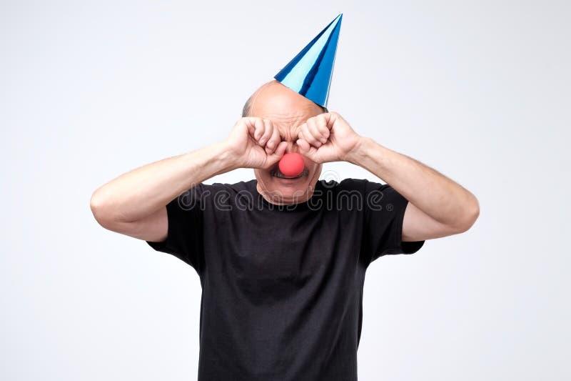 Uomo senior in cappuccio di compleanno che grida e che pulisce gli strappi sul suo partito immagini stock libere da diritti