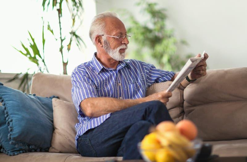 Uomo senior a casa che legge giornale immagini stock