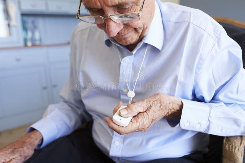 Uomo senior a casa facendo uso del pulsante di chiamata dell'allarme di emergenza fotografie stock