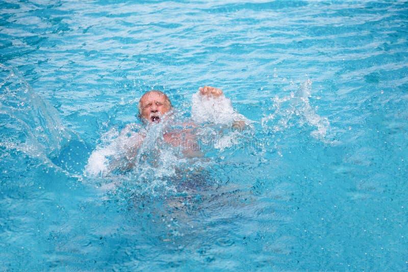 Uomo senior che annega nella piscina fotografia stock
