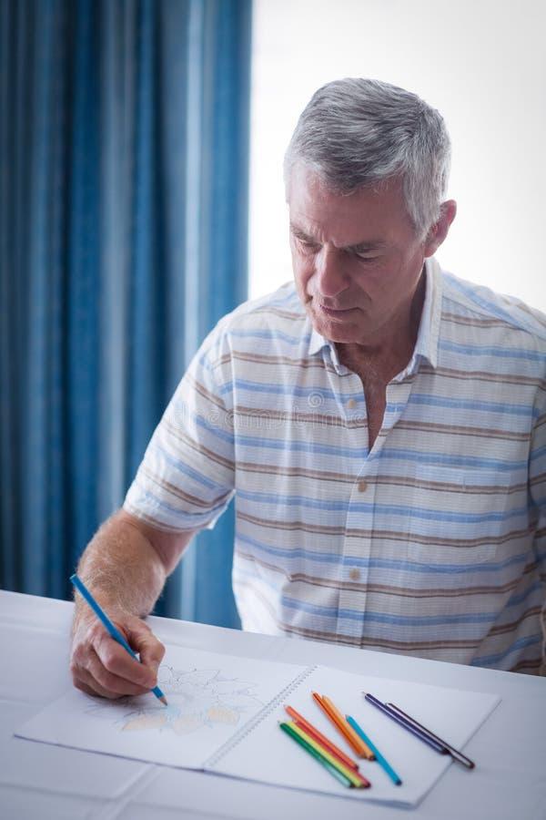 Uomo senior che assorbe album da disegno fotografia stock
