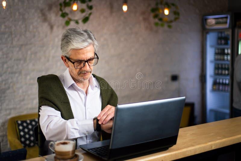 Uomo senior che controlla tempo mentre facendo uso del computer portatile in una barra fotografia stock libera da diritti