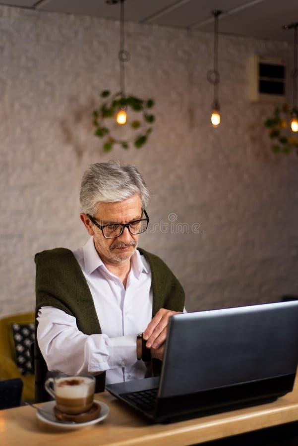 Uomo senior che controlla tempo mentre facendo uso del computer portatile in una barra fotografie stock libere da diritti