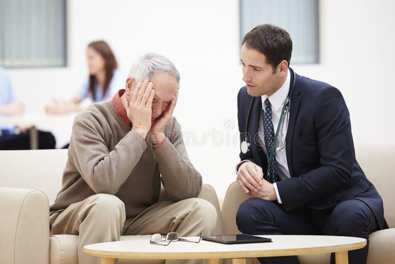 Uomo senior che discute i risultati dei test con medico immagini stock libere da diritti