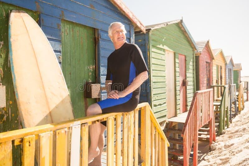 Uomo senior che distoglie lo sguardo mentre sedendosi sul recintare della capanna fotografia stock libera da diritti