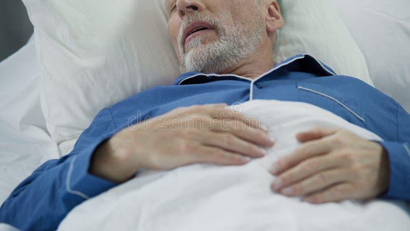 Uomo senior che dorme a letto e che russa, problemi con sonno, sanità fotografia stock libera da diritti