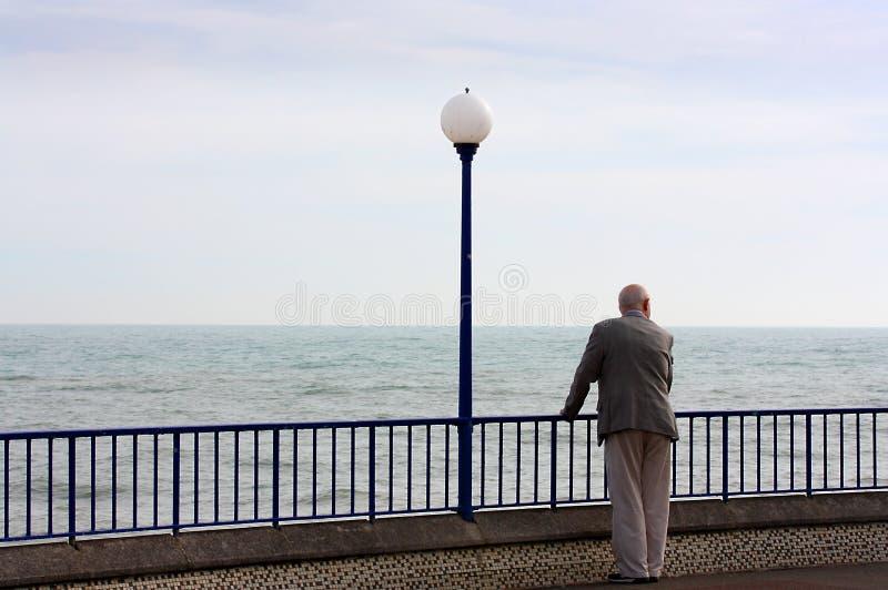 Uomo senior che esamina mare in passeggiata di Eastbourne in Sussex fotografie stock libere da diritti
