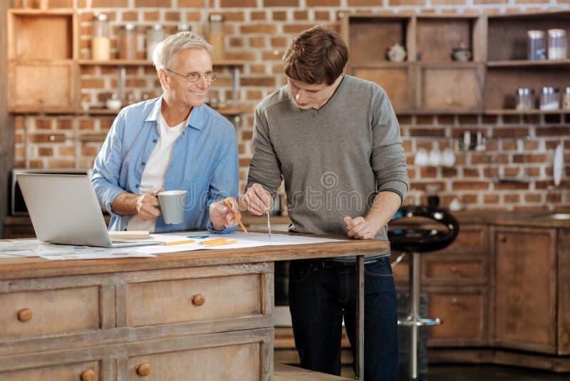 Uomo senior che esprime al suo giovane collega parere circa il disegno fotografia stock libera da diritti