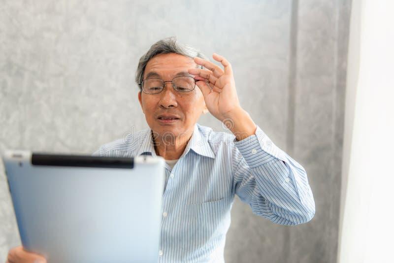 Uomo senior che ha problemi di vista mentre sta utilizzando una compressa immagini stock