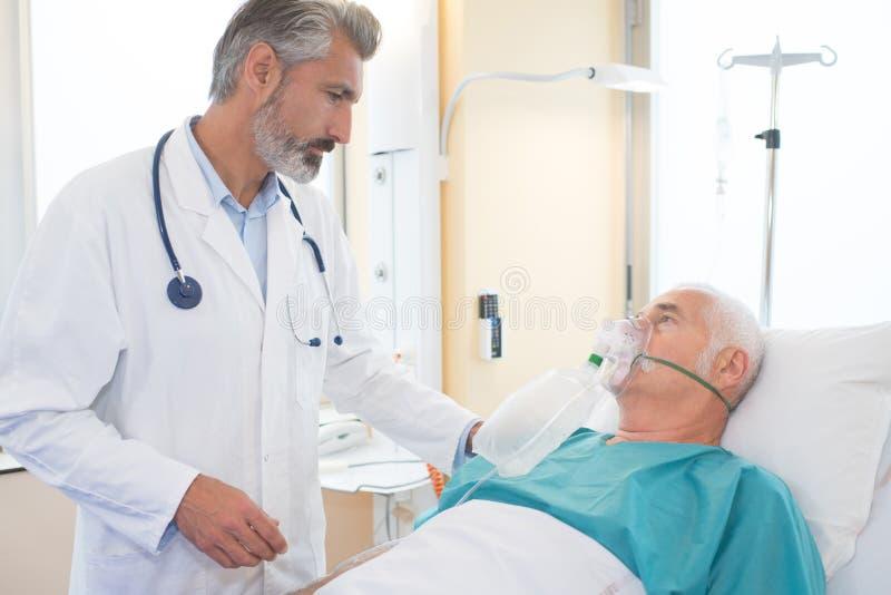 Uomo senior che inala attraverso la maschera di ossigeno in clinica immagine stock